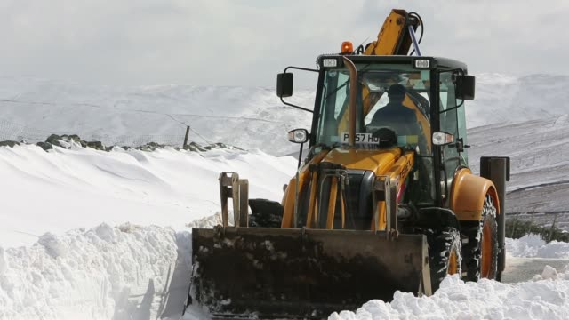 a jcb tries to clear a way through massive snow drifts blocking the kirkstone pass road above ambleside in the lake district, uk during the extreme weather event of late march 2013. shot taken on 25th march 2013. - road closed sign stock videos & royalty-free footage