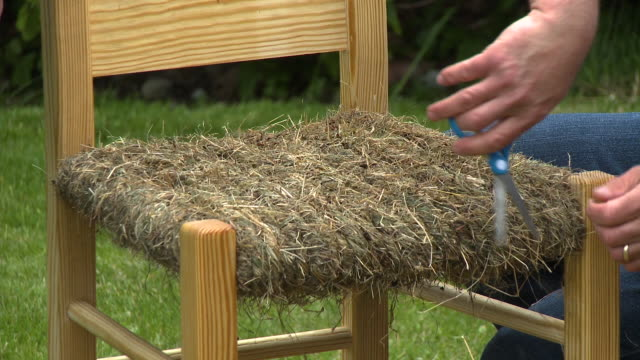 trimming chair seat made of hay - schere stock-videos und b-roll-filmmaterial