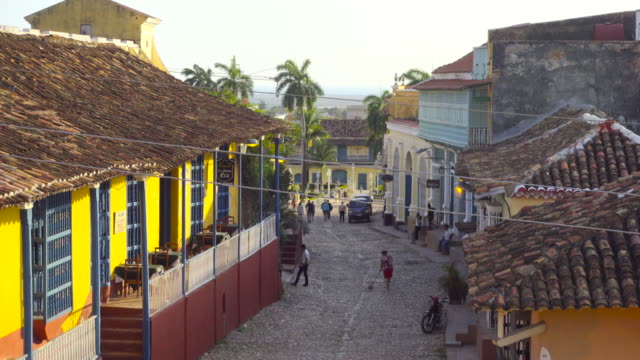 trinidad cuba establishing shot from high point of view lookout. colonial style town with colorful yellow house, tile roof and street cobbles / cobblestone. people walking on the street. travel like a local - brief - sancti spiritus province stock videos and b-roll footage