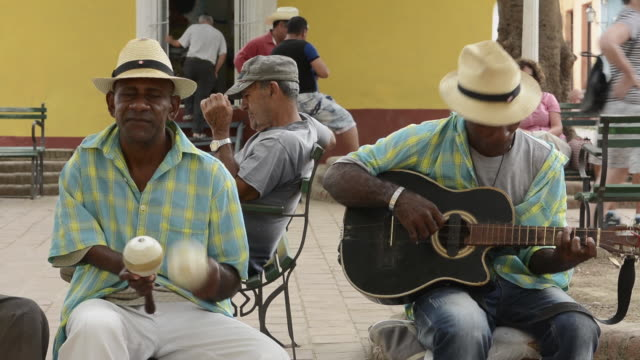 vidéos et rushes de trinidad cuba in park with men playing music in park and singing band - guitare