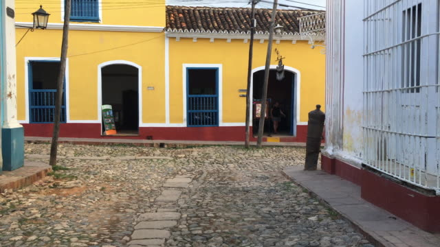 trinidad, cuba: point of view of tourist walking in colonial cobblestone street surrounded by colonial houses - major road bildbanksvideor och videomaterial från bakom kulisserna