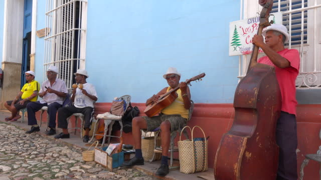 vidéos et rushes de trinidad, cuba: seniors acoustic band busking or playing music in a cobblestone street of the colonial city which is a unesco world heritage - cuba
