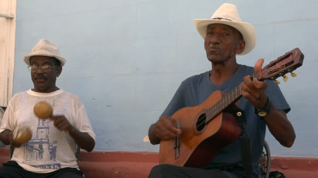 trinidad, cuba: street musicians playing acoustic instruments for the delight of tourists visitors to the unesco world heritage site. - cuba stock videos & royalty-free footage