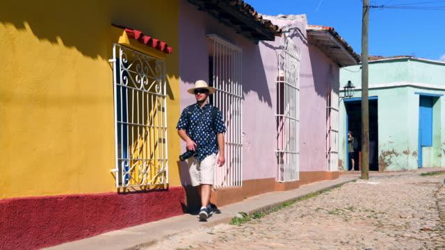 trinidad, cuba: tourist man walking the cobblestone colonial streets of the old village - キューバ点の映像素材/bロール
