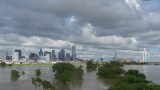 T/L WS  Trinity River at major flood stage, Dallas, Texas skyline, dramatic clouds
