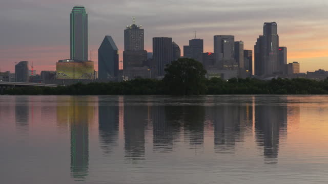 Trinity River at major flood stage in Dallas, Texas, downtown Dallas buildings reflecting in water at dawn, Omni Hotel sign says SMILE