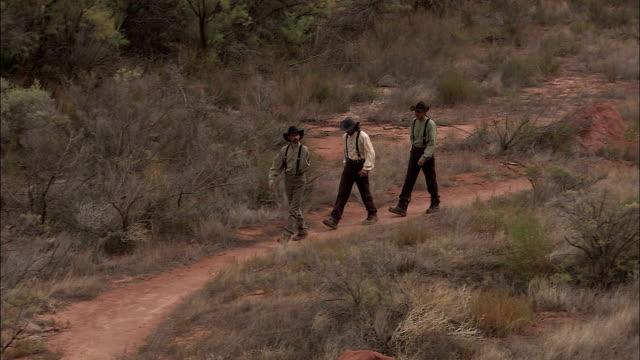 a trio of explorers walk along a dusty path. - historische szene stock-videos und b-roll-filmmaterial