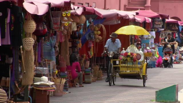 zo trishaw gliding past shopping stalls / malacca, malaysia - malacca stock videos and b-roll footage