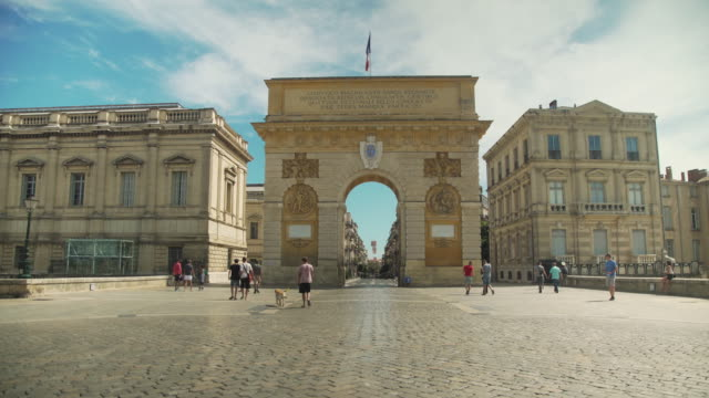 triumphal arch porte du peyron at montpellier, iconic image of france with french flag - モンペリエ点の映像素材/bロール