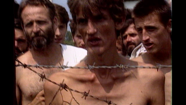 Trnopolje EXT Malnourished prisoners behind fence in Serbianrun detention camp prisoners jogging through camp and prisoners interviewed from behind...