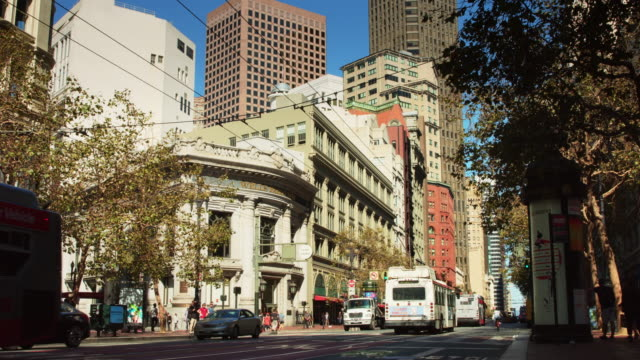 trolley buses and cyclists on market st, san francisco - trolleybus stock-videos und b-roll-filmmaterial