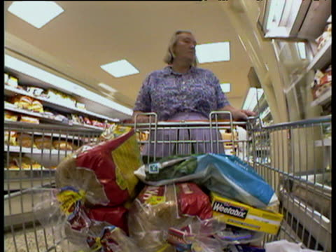 vídeos de stock e filmes b-roll de trolley camera looking at woman pushing trolley around supermarket while collecting groceries - vendas