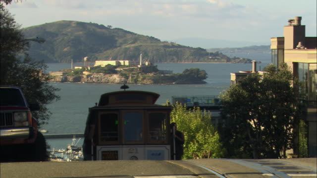 vídeos y material grabado en eventos de stock de ms trolley car on steep san francisco street, alcatraz island in background / california, usa - bahía de san francisco