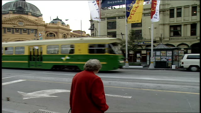 trolley car passing on street and pan to melbourne city map on road side - trolleybus stock-videos und b-roll-filmmaterial