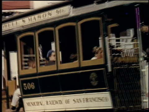 1957 ts trolley going down hilly street with people riding / san francisco, california, united states - tram stock-videos und b-roll-filmmaterial