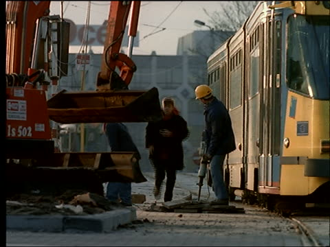 trolley moving past road construction worker + machine - baugerät stock-videos und b-roll-filmmaterial