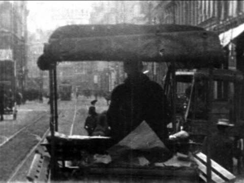 B/W 1906 trolley point of view behind cart on Boston city street / newsreel
