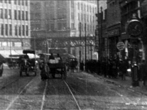 B/W 1906 trolley point of view people on sidewalk past stores + trolleys on Boston city street / newsreel