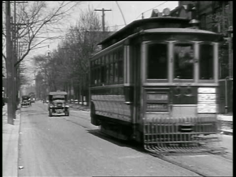 vídeos de stock e filmes b-roll de b/w 1919 trolley stopping on street / couple gets out + is hit by car behind it / newsreel - 1919