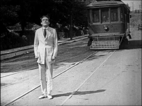 vídeos y material grabado en eventos de stock de b/w 1920 trolley switching tracks to avoid man standing in middle of street / feature - sólo hombres jóvenes
