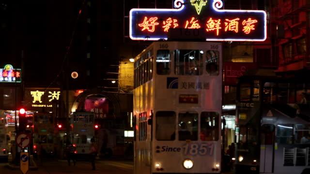 ws trolley tram passing through street at night / hong kong, china - trolleybus stock-videos und b-roll-filmmaterial