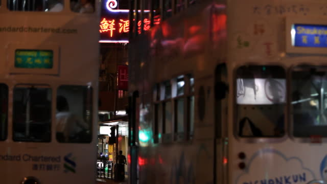 ms  trolley tram passing through street at night / hong kong, china - trolleybus stock-videos und b-roll-filmmaterial