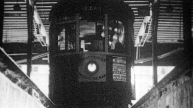 trolley tram pulls into round house for repairs / african american worker walks under tram to inspect / inside trolley making repairs through a hole... - 1937 stock videos and b-roll footage