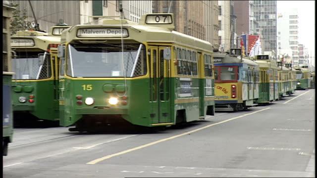 trolleys going by camera in melbourne australia - trolleybus stock-videos und b-roll-filmmaterial