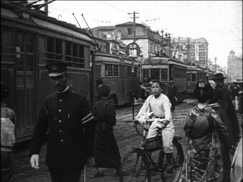 b/w 1923 pan trolleys + pedestrians on tokyo street / japan / newsreel - 1920 stock-videos und b-roll-filmmaterial