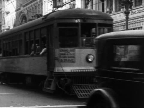 b/w 1930 trolleys + traffic driving on city street / los angeles, ca - tram stock-videos und b-roll-filmmaterial