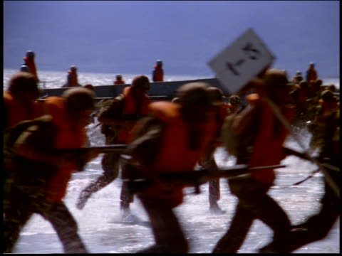 pan troop of marine in life preservers storming beach from the sea / rio de janeiro, brazil - cinematography stock videos & royalty-free footage