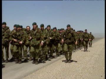vídeos y material grabado en eventos de stock de troop of royal marines walking in row on desert road under blue sky northern iraq. - royal marines