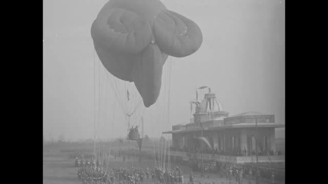 troop review with hot air balloons / people in the reviewing stand / crowd watches as tanks and cannons ride by / jugglers and women in ethnic dress... - principe persona nobile video stock e b–roll