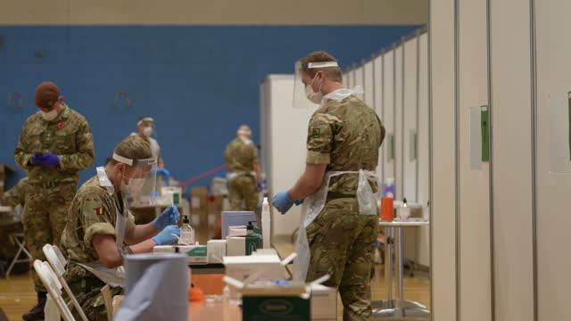 stockvideo's en b-roll-footage met troopers from the king's royal hussars, who normally crew main battle tanks, conduct coronavirus flow tests on members of the public at a testing... - british military
