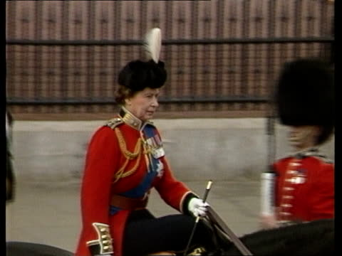 trooping the colour; 12.45: queen leads procession from buckingham palace; queen watches colours handed over, horseguards parade; takes salute. cas... - 軍旗分列行進式点の映像素材/bロール