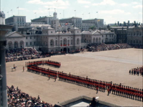 trooping the colour; england: london: horse guards parade: queen rides right-left onto horse guards parade colour handed to youngest guardsman crowd... - 軍旗分列行進式点の映像素材/bロール