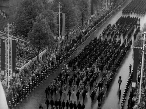 troops and military bands parade up the mall as they head back to buckingham palace during the coronation procession 1953 - kopf nach hinten stock-videos und b-roll-filmmaterial