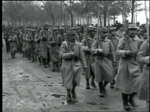 wwi troops carrying rifles march in formation through muddy street / france - 1918 stock videos and b-roll footage