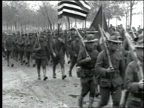 wwi troops carrying rifles march in formation through muddy street carrying us flag / france - 1918 stock videos & royalty-free footage