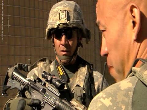 us troops converse with man whilst on patrol in afghanistan 28 january 2010 - 2001年~ アフガニスタン紛争点の映像素材/bロール