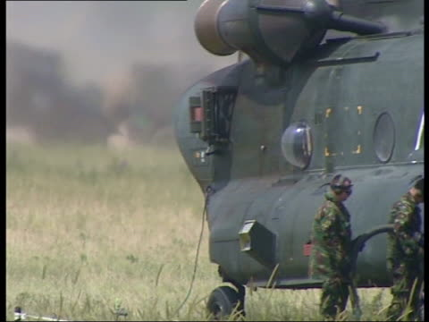 NATO troops enter Kosovo Chinook helicopter landing / helicopters carrying military equipment slung beneath them and lowering them to the ground /...