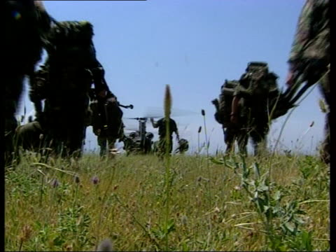 nato troops enter kosovo puma helicopter taking off / chinook helicopter in field with rotors turning as second chinook comes in to land / soldiers... - helicopter rotors stock videos and b-roll footage