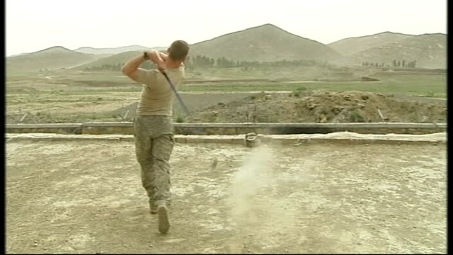 vidéos et rushes de tirzaye troops hitting golf balls from top of roof - swing de golf
