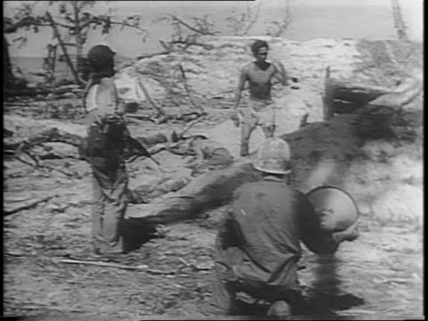 Troops fighting on decimated island with palm trees in the background / montage of soldier in hole firing rocket launcher soldiers firing on Japanese...
