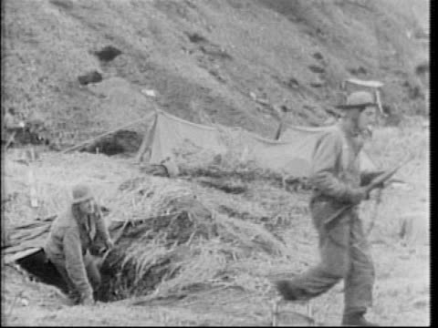 us troops in camp in valley on attu island during world war ii / soldiers eat / four soldiers emerge from foxhole / montage soldiers examine a downed... - military camp stock videos & royalty-free footage