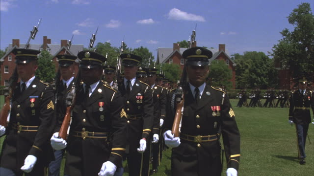 Troops in dark dress uniforms carrying rifles march in military ceremony.