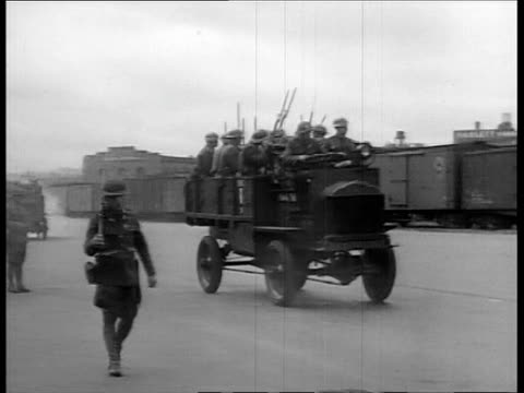 vídeos y material grabado en eventos de stock de troops in trucks arriving at train station to break dock workers strike / soldiers loading machine gun with bullets / soldiers with machine guns... - 1934