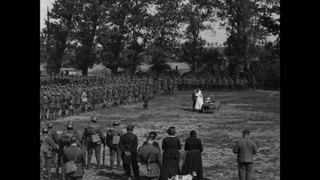vidéos et rushes de troops lined up for outdoor mass, priest in middle of unit, including hals of men praying and receiving communion. - prêtre