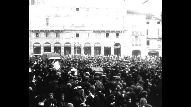 Troops march along a street in Verona / wide shot of a square packed with civilians waving as trucks and troops move through / street level shot of...