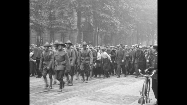 wwi troops march in paris street as they join parisians' celebration of us independence day / women join the procession and french soldiers and... - army soldier stock videos & royalty-free footage